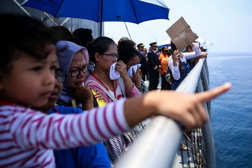 Attendees gathered on the deck of a ship that was ferried out to the crash site where Lion Air flight JT-610 plunged into the ocean at high speed.