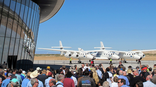 In this Oct. 17, 2011, file photo a crowd gathers outside Spaceport America for a dedication ceremony as Virgin Galactic's mothership WhiteKnightTwo sits on the tarmac near Upham, New Mexico.