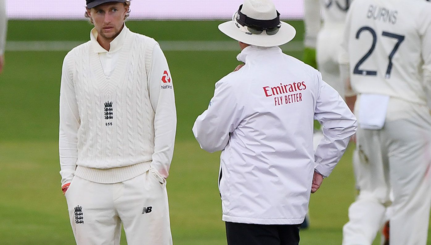 Joe Root speaks to umpire Richard Illingworth as bad light finally stops play on day three of the third Test.