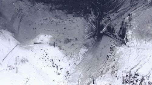 Aerial images showed sections of the snowy mountain covered in dark ash. (AP)