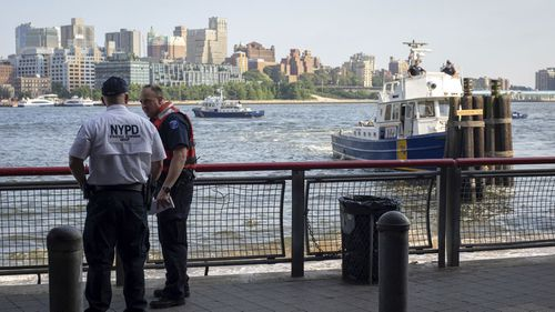 Police at the spot where the baby was found in the New York river.