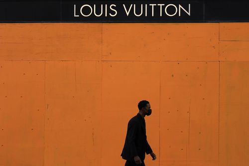 A man walks past a boarded-up window at a Louis Vuitton store in San Francisco, Sunday, Nov. 1, 2020, ahead of Election Day. (AP Photo/Jeff Chiu)