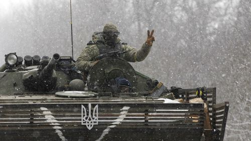 A Ukrainian soldier in a tank displays the peace sign. (AAP)