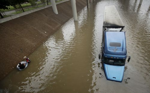 An unidentified man helps Carlos Torres, in tube, get to dry ground after Torres drove his tractor-trailer into a freeway flooded by Hurricane Harvey. (AAP)