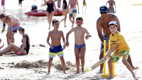 Children play a game of cricket at the beach. (AAP)