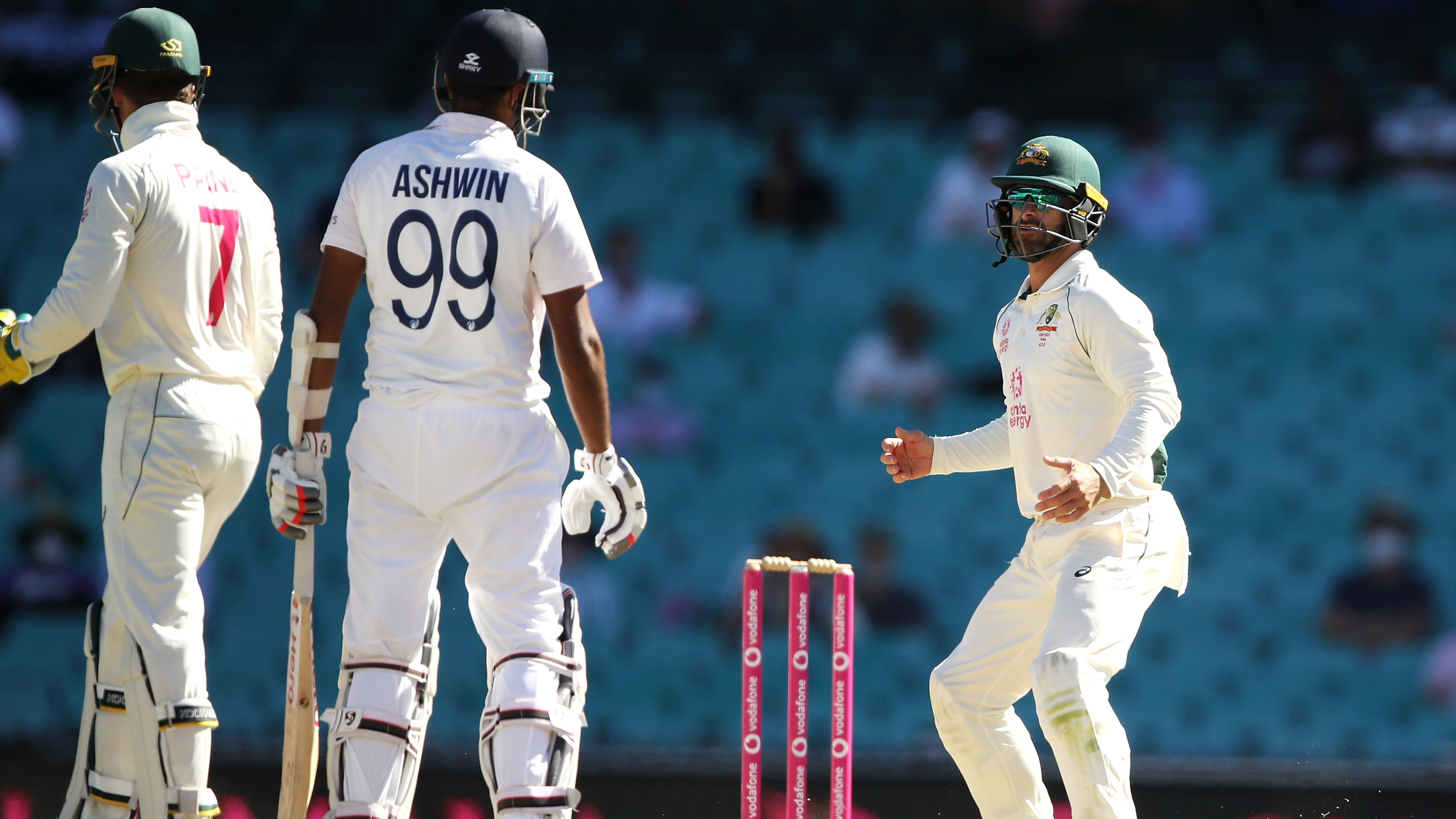 Ravichandran Ashwin of India speaks to Matthew Wade of Australia.