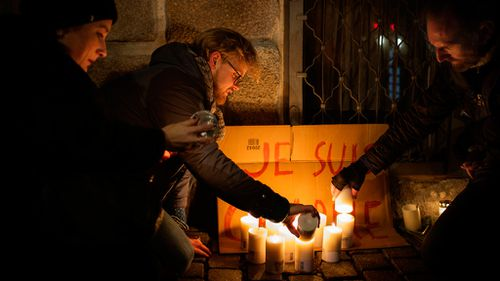 People light candles in front of the French Embassy in Copenhagen, Denmark as mark of respect to those killed in the Charlie Hebdo shooting. (AAP)