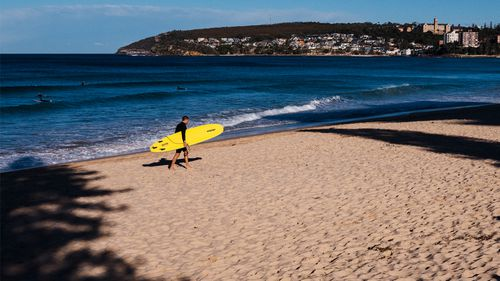 A lone surfer walks across Manly Beach, as the lockdown in Sydney edges closer to its fifth week.