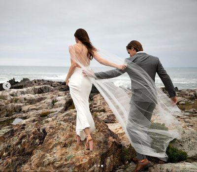 Barbara and husband Craig traverse some rocks to pose for wedding photos.