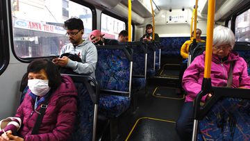Passengers sit apart on a Sydney bus travelling down King street in Newton.
