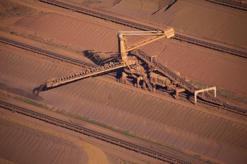 An iron ore stacker feeds stockpiles at Rio Tinto iron ore mine site in the Pilbara region of Western Australia.