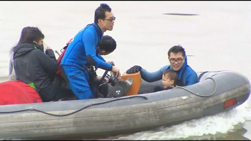 Rescued passengers are taken to shore for transport to local hospitals.