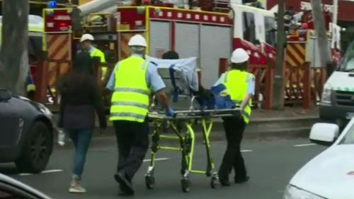 Emergency services helping the injured after man sets himself on fire in Springvale Commonwealth Bank branch.