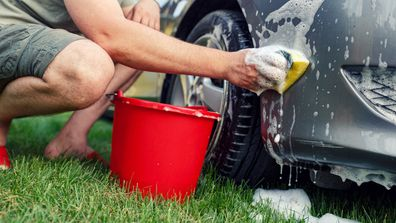 Young male washing car with a sponge and foam
