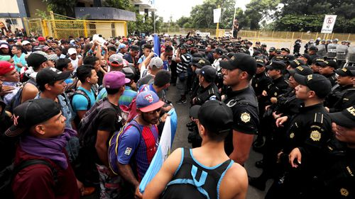 several Guatemalan police officers and migrants were injured as the group kicked and pushed its way through the gate on the Guatemalan side of the border.