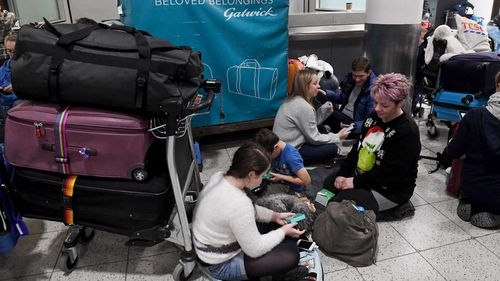 People sit on the ground beside their luggage inside Gatwick Airport.