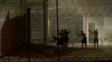 Police could be heard over a loudspeaker urging inmates to put down their weapons and surrender or face serious consequences.