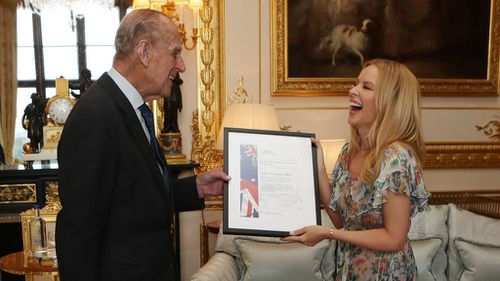 The Duke of Edinburgh presents Kylie Minogue with the 2016 Britain-Australia Society Award. (AAP)