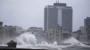 Waves surge over a sea wall in Havana. (AAP)