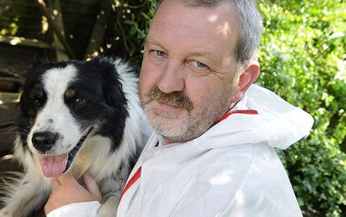 Mick Swindells, a former police officer with Lancashire Police, is photographed alongside one of his cadaver dogs.