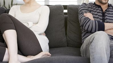 Unhappy couple sitting at home