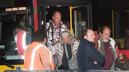 Tourists and locals disembark a bus at the Horncastle Arena in Christchurch after being evacuated by the HMNZS Canterbury Naval ship from Kaikoura. (AFP)