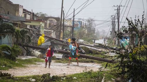 Residents walk near downed power lines felled by Hurricane Irma in Caibarien. (AAP)