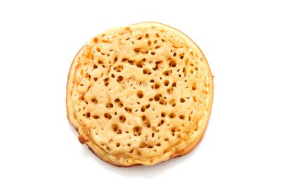 Two crumpets with thick-spread peanut butter and 250ml glass of milk