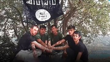 A group of young men pose in front of the Islamic State flag.