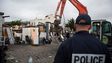A policeman looks at a mechanical digger destroying a Roma camp after it was cleared by authorities on July 21, 2015 in Bobigny, northeast of Paris. (AFP)