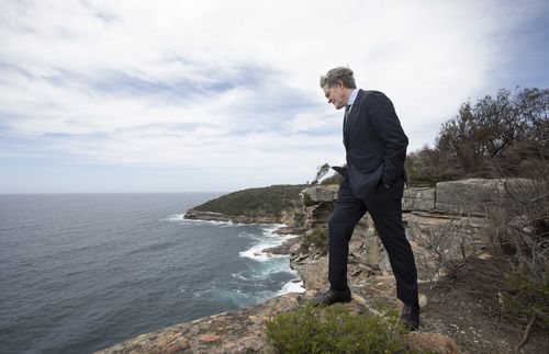 Steve Johnson, the brother of murdered Scott Johnson, looks down to the rocks and ocean below at the point along the cliff at Blue Fish Point, North Head, Manly where his brother fell to his death 30 years ago.
