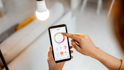 Woman adjusting a smart light bulb with her phone