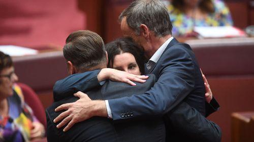Jacqui Lambie receives a hug by Australian Greens Senators Nick McKim and Peter Whish-Wilson (Image: Facebook)