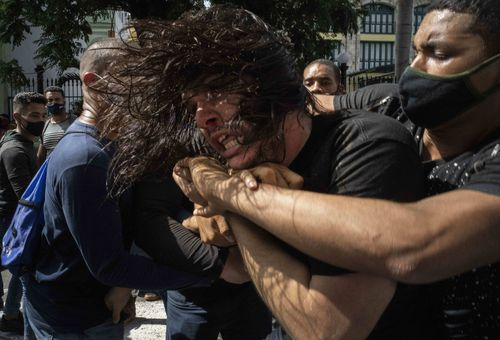 Plainclothes police detain an anti-government protester during a protest in Havana, Cuba, Sunday, July 11, 2021. Hundreds of demonstrators went out to the streets in several cities in Cuba to protest against ongoing food shortages and high prices of foodstuffs, amid the new coronavirus crisis. (AP Photo/Ramon Espinosa)