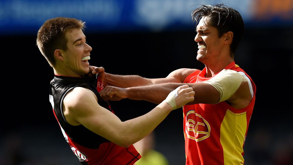 Zach Merrett of the Bombers and Aaron Hall of the Suns go at it (AAP)