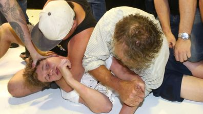 Egg-boy is put in a chokehold by some of Fraser Anning's supporters.