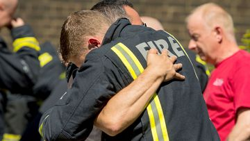 A firefighter embraces a man after an emotional minute's silence at the scene of the Grenfell Tower tragedy in London. (AAP)