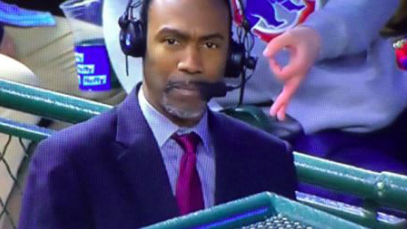 A fan makes a racist gesture behind baseball analyst Doug Glanville.