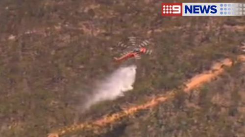 A helicopter waterbombs a fire at Sampsons Flat, in South Australia's Mount Lofty ranges. (9NEWS)