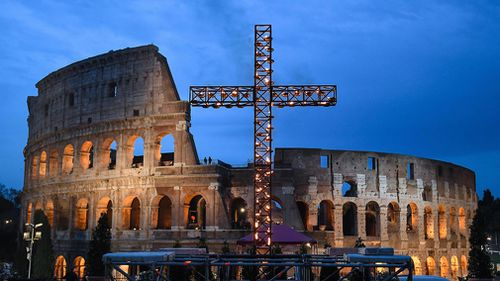 A candle-lit cross stands outside the ancient Colosseum in Rome, Italy. (EPA)