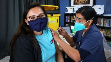 An NSW Health worker administers a Pfizer COVID-19 vaccine to a client at the Australian Sikh Association (ASA) pop up clinic in Sydney.