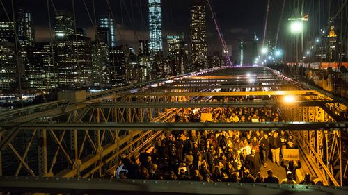 Protesters walk across the Brooklyn Bridge in New York during the National March Against Police Violence. (Getty)