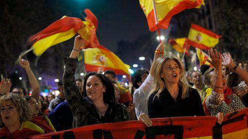Anti-independence supporters shout slogans and wave Spanish flags as they march against the unilateral declaration of independence. (AP)