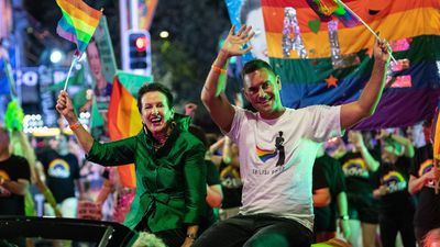 Clover and Alex wave their rainbow flags with pride