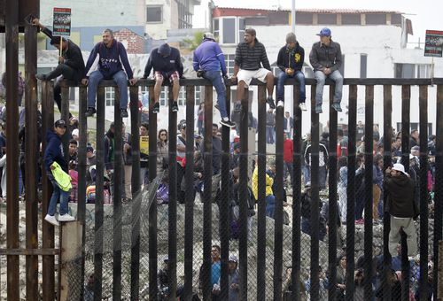 The refugees sit on top of the border wall on the beach during a gathering of migrants living on both sides of the border. (AAP)