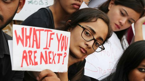 An Indian National Congress supporter holds a placard as he participates in a public outrage rally in New Delhi. (EPA)
