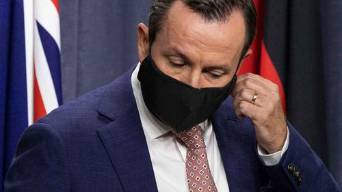 WA Premier Mark McGowan takes off his mask.