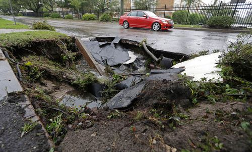 A car travells past a sinkhole in downtown Wilmington, North Carolina, after Hurricane Florence travelled through the area in September 2018.