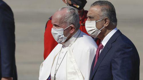 Paus Fransiskus diapit oleh Perdana Menteri Irak Mustafa al-Kadhimi setibanya di bandara internasional Baghdad, Irak, Jumat, 5 Maret 2021.