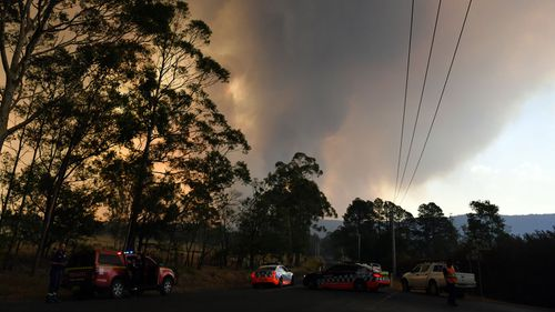 Police form a road block at a bushfire in North Nowra, 160km south of Sydney, Saturday, January 4, 2020.